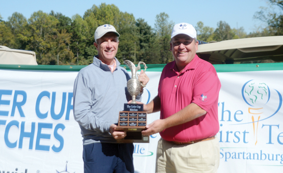 Greenville captain Terry Willis receives the Cyder Cup from Spartanburg captain Max Fain.